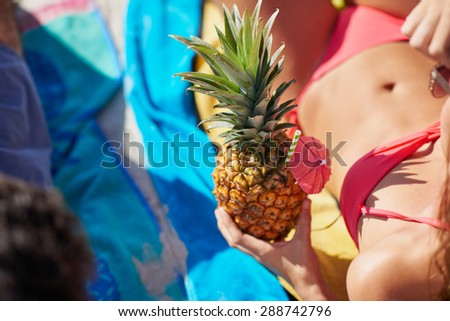 Close up shot of attractive woman holding pineapple cocktail on the beach angle shows unrecognizable body - stock photo