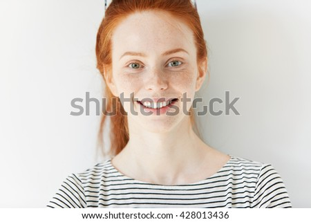 Close up shot of beautiful Caucasian student girl with ginger hair and freckles wearing sailor shirt looking at the camera with happy confident smile, achieving life goals. Youth and happiness concept - stock photo