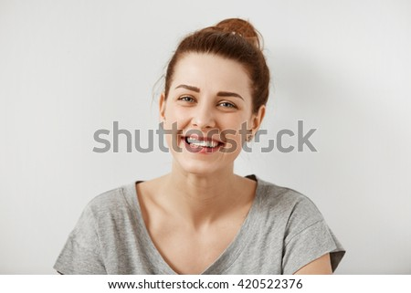 Close up shot of beautiful young redhead woman in gray T-shirt looking with cute smile at the camera while posing isolated against white concrete wall background. Human face expressions and emotions  - stock photo