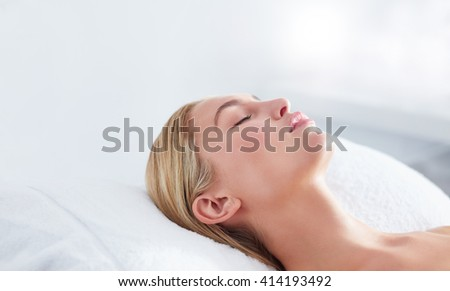 Close up shot of beautiful young woman relaxing on massage table at spa. Female lying with her eyes closed. - stock photo