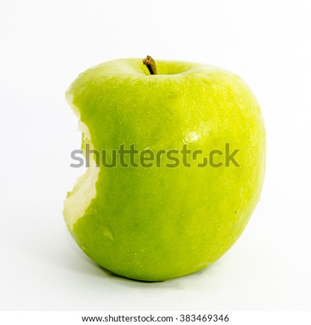 close up shot of bitten green apple with white background - stock photo