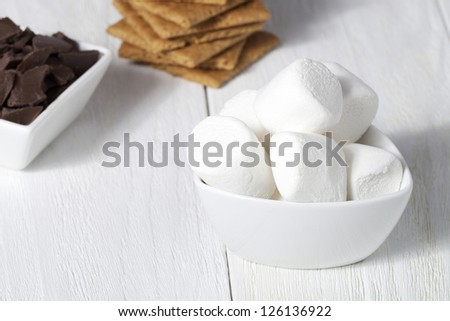 Close-up shot of bowl with marshmallow, chocolate and graham crackers. - stock photo