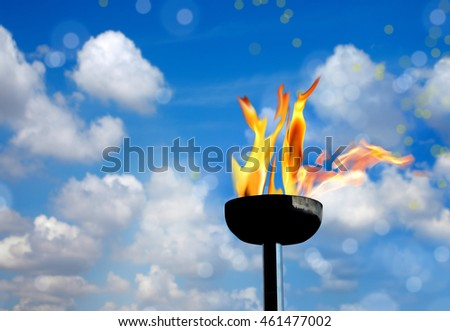 close up shot of burning flaming torch over cloudy sky.