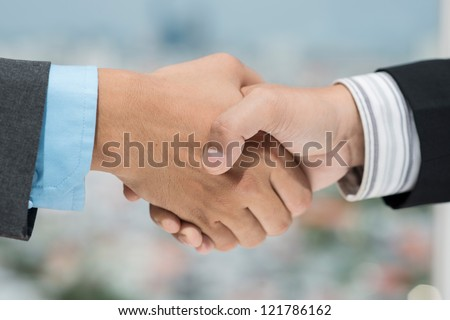 Close-up shot of business people shaking hands expressing trust and respect