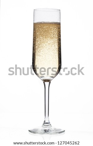 Close-up shot of champagne flute full of alcoholic drink and bubbles over white background.