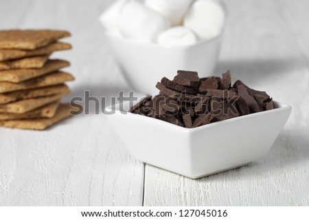 Close-up shot of chocolate chips in bowl with other smores ingredient in background. - stock photo
