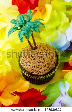 Close-up shot of cupcake with plastic coconut tree miniature surrounded by colorful flowers.