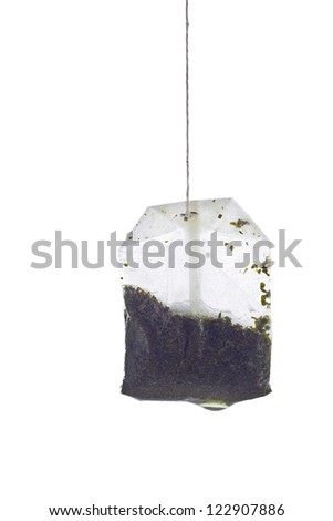 Close-up shot of dipped tea bag on white background. - stock photo