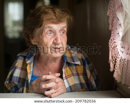 Close-up shot of elderly woman sitting at table in his house. - stock photo