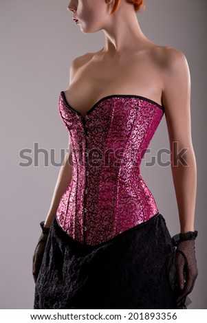 Close-up shot of elegant young woman in pink corset with floral pattern, studio shot  - stock photo
