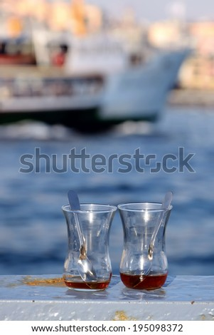 Close up shot of emptied traditional tea glasses on the railings by the sea in Eminonu district in Istanbul Turkey - stock photo