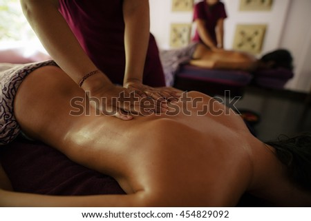 Close up shot of female massage therapist hands massaging man at spa center. Focus on hands of masseuse. - stock photo