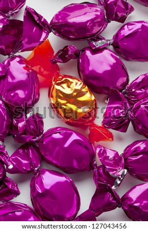Close-up shot of golden and purple hard candies over white. - stock photo