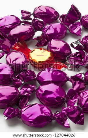 Close-up shot of golden candy in between of purple candies. - stock photo
