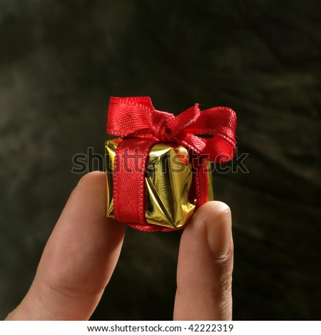 close up shot of golden color giftbox in hand - stock photo