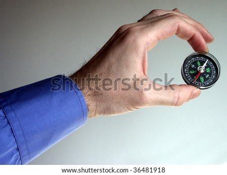 close up shot of hand holding compass - stock photo