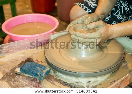 close up shot of hand working on potter at the pottery wheels, with selective focus and shallow dof  - stock photo