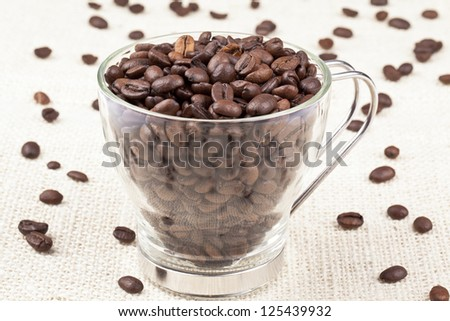 Close-up shot of heap of coffee beans in coffee mug. - stock photo