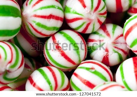 Close-up shot of heap of colorful peppermint candies with green and red stripes. - stock photo