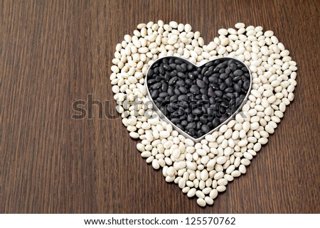 Close-up shot of heart shape beans on wooden table. - stock photo