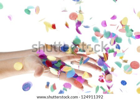 Close-up shot of human hands touching decorative colorful confetti against plain white background. - stock photo