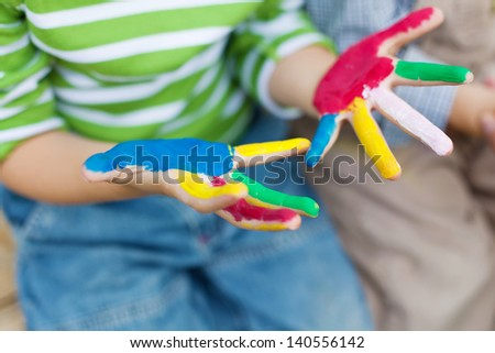 Close up shot of little child showing colorful painted hands - stock photo