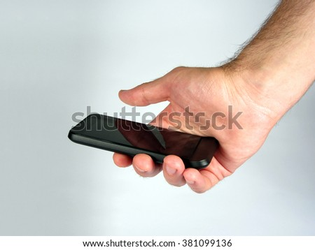 Close up shot of male hand holding smartphone with touchscreen display. - stock photo