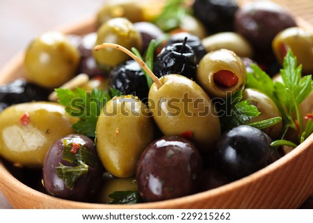 Close-up shot of marinated olives with herbs and spices in wooden plate. - stock photo