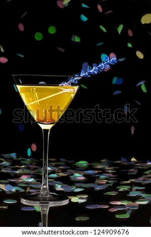 Close-up shot of martini glass with orange drink and straw with confetti over dark background. - stock photo