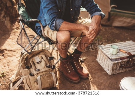 Close up shot of mature man sitting on a chair. Man relaxing at campsite, focus on hands. - stock photo