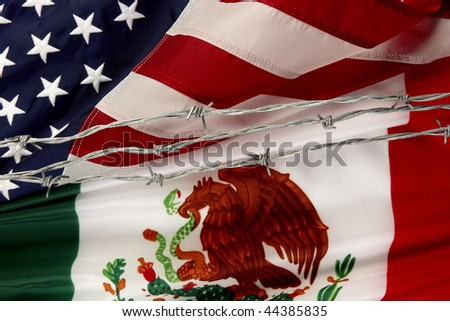 Close-up shot of Mexican and US flags separated by barbed wire - stock photo