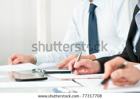 Close up shot of people compiling forms during a business conference - stock photo
