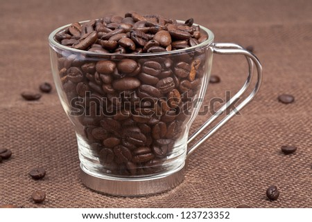 Close-up shot of pile of coffee beans in coffee mug while some scattered on table cloth. - stock photo