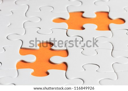 close up shot of plain puzzle with two missing pieces - stock photo