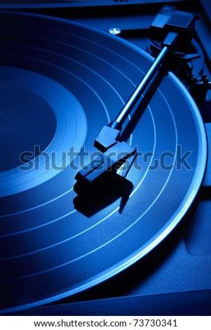 Close up shot of record player with moody blue lighting - stock photo