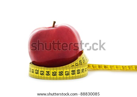 close up shot of red apple with yellow measuring tape isolated on white background - nutrition, healthcare and diet concept - stock photo