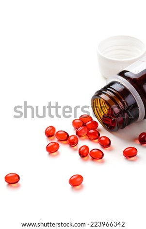 Close up shot of red capsules isolated on white background. - stock photo