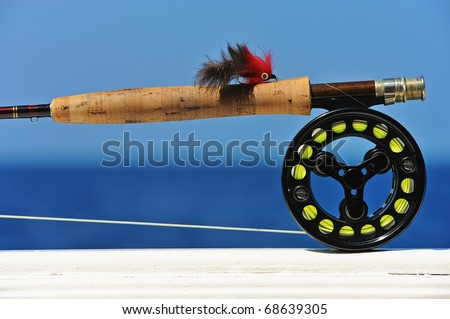 Close up shot of saltwater fly fishing tackle against sea - stock photo