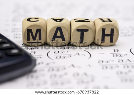 Close up shot of scientific calculator and mathematical equations sheets. Wooden letter blocks assemble the word mathematics