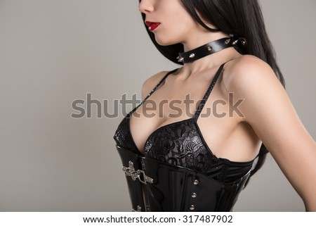 Close-up shot of sensual gothic girl in black fetish corset, bra, and spike choker  - stock photo