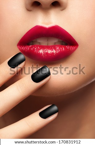 Close-up shot of sexy woman lips with red lipstick and beautiful black manicure - stock photo
