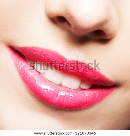 Close-up shot of smiling female mouth with red lips make-up - stock photo