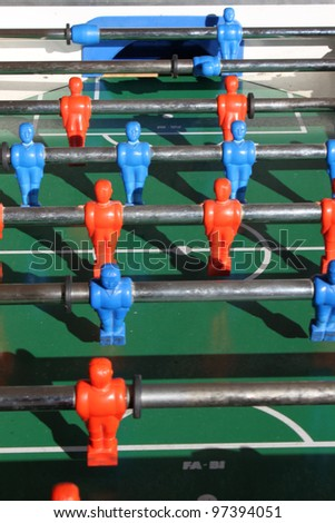Close up shot of soccer table game with green field and red and blue plastic football players