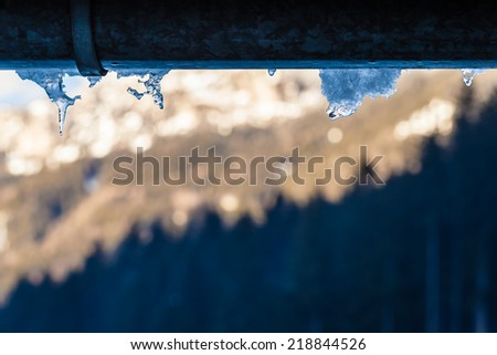 close up shot of some icicles hanging from the gutter - stock photo