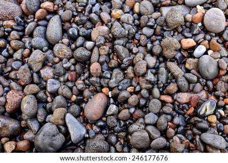 Close up shot of some wet volcanic pebbles - stock photo