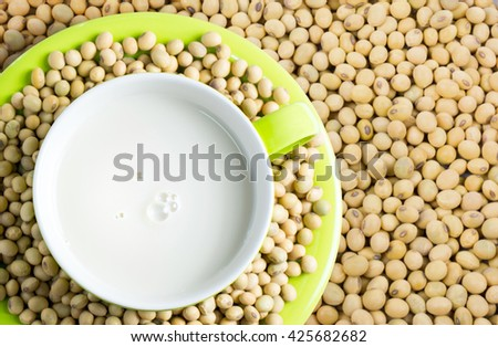 Close up shot of soybeans food background. Soy milk ,Soya milk in green cup and soy bean in background. Top view. - stock photo