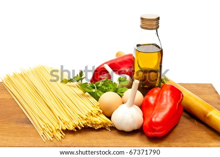 Close-up shot of spaghetti and vegetables on wooden board. Studio shot - stock photo