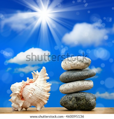 close up shot of stone pile and seashell over sunny sky - stock photo