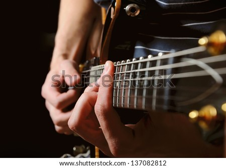 close up shot of strings and guitarist hands playing guitar over black - shallow DOF with focus on hands
