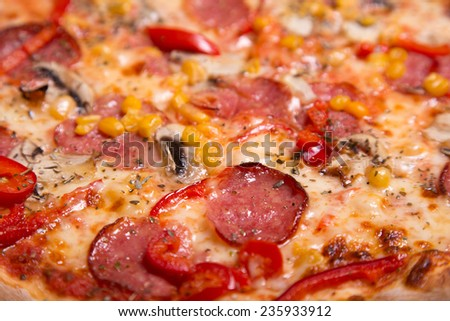 Close-up shot of tasty American pizza with pepperoni and mushrooms, selective focus   - stock photo